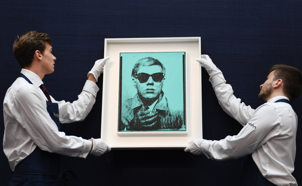 epa06045478 Sotheby's Auction House staff hold Andy Warhol's first self- portrait during Sotheby's Contemporary Art sale in London, Britain, 23 June 2017. The artwork is expected to fetch 6-8 million euros at auction 28 June  EPA/ANDY RAIN